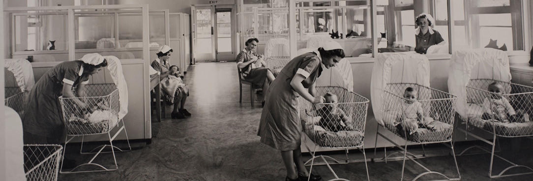 Black and white photo, hospital ward with babies in cots being tended to by nursing staff.