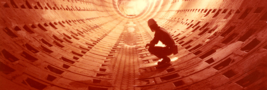 A photograph of a workman in a tunnel
