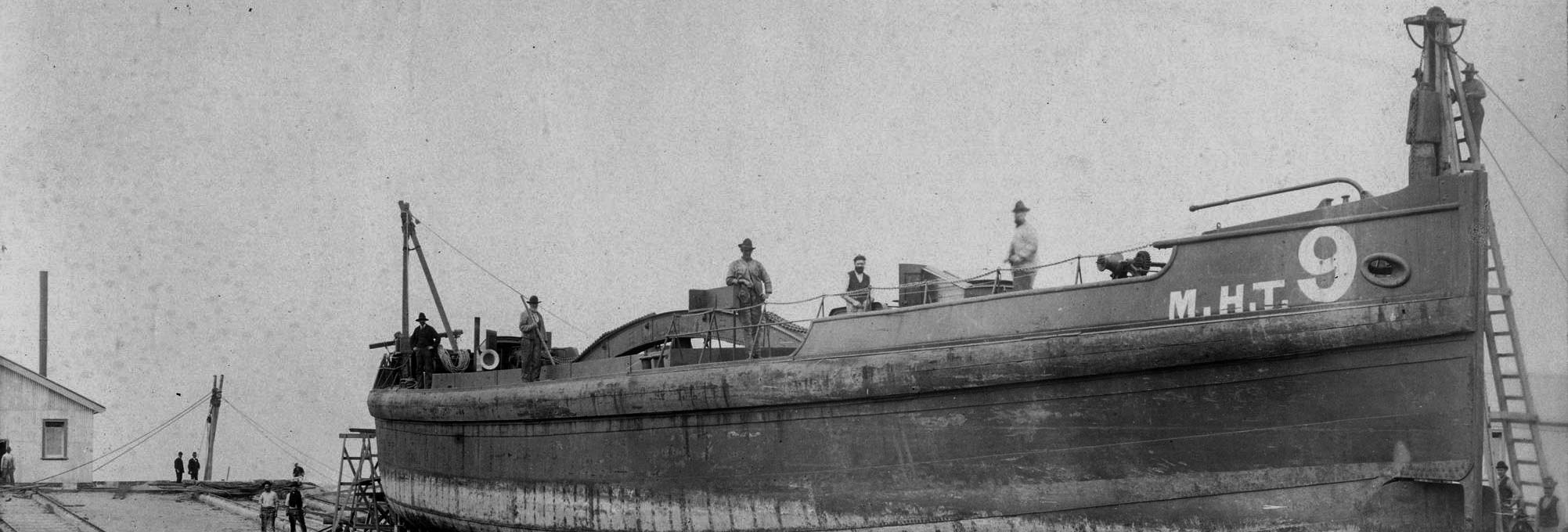 Black and white photo of a ship with crew
