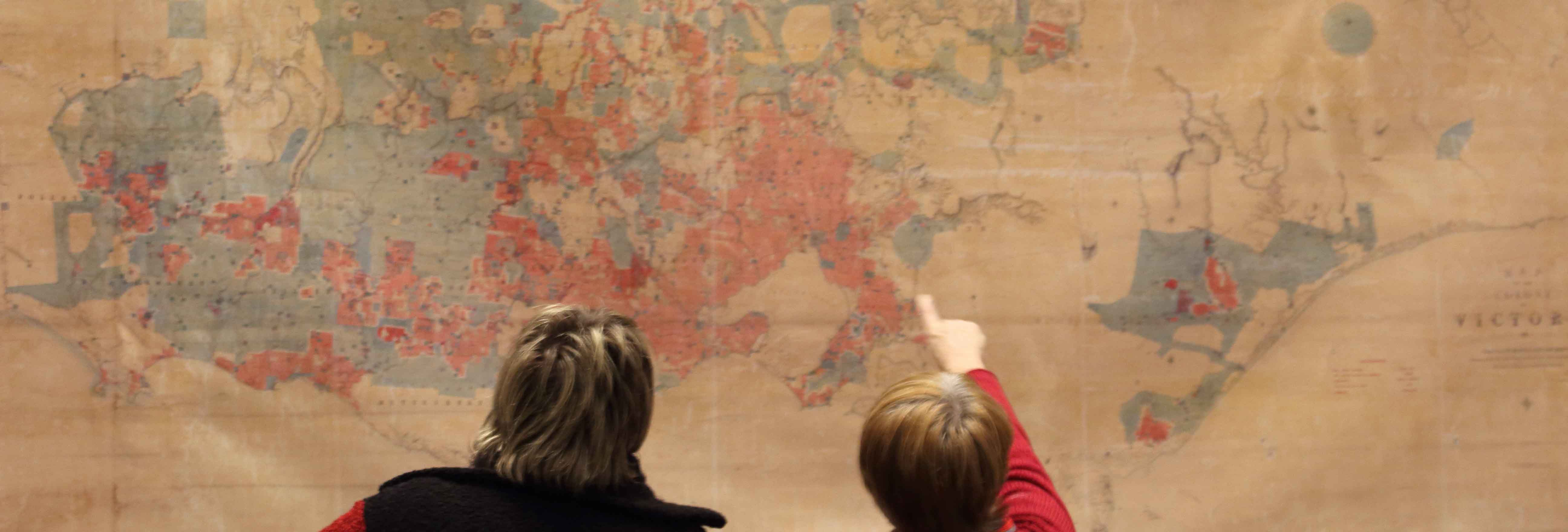 People looking at a wall-hanging map