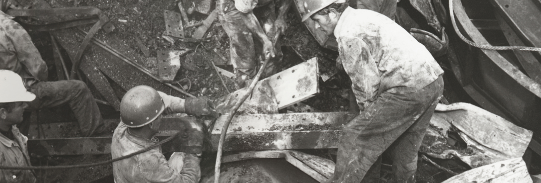 Black and white photo, rescuers searching through the rubble for survivors after the bridge collapse.