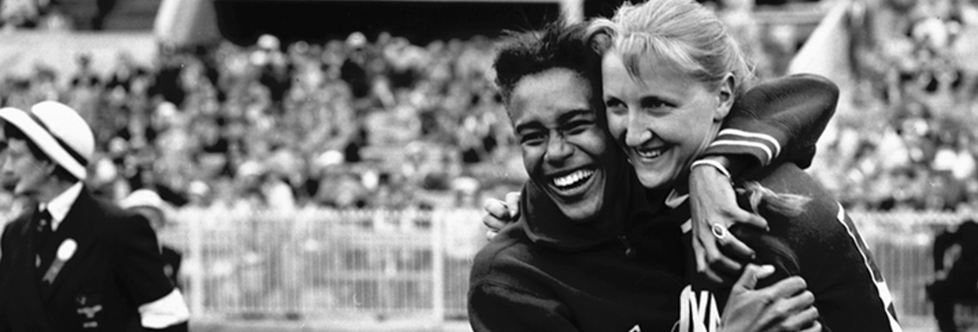 A black and white photo of two women hugging at the 1956 Olympic games