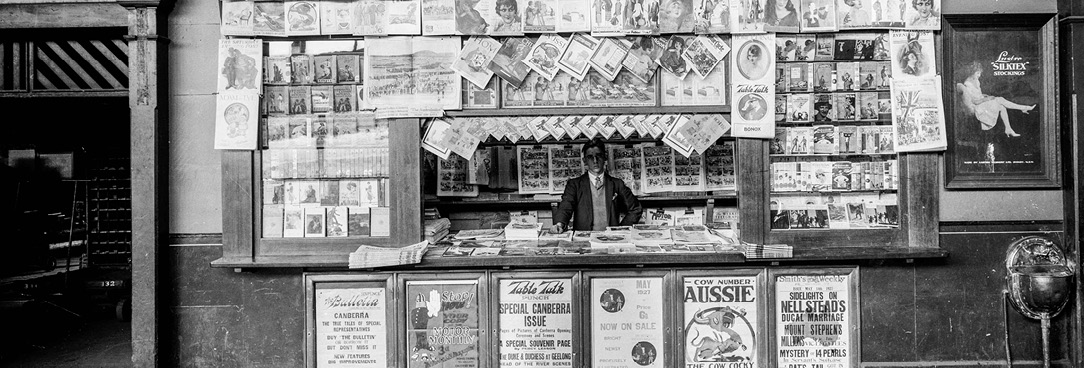 Black and white photograpgh of man standing behind Newspaper stand at Spencer St train station, July 1930