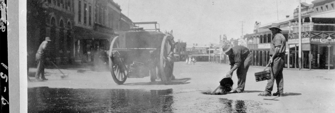 black and white photo of men pouring water on road