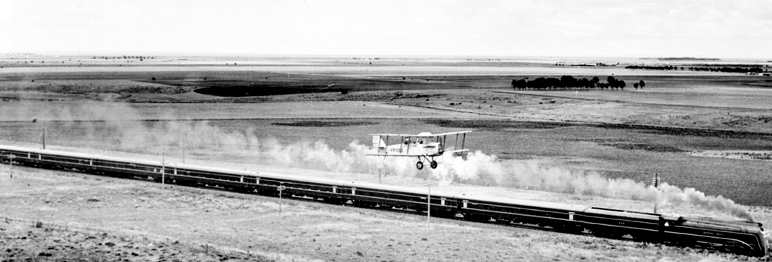 Black and white photo of a plane and a train