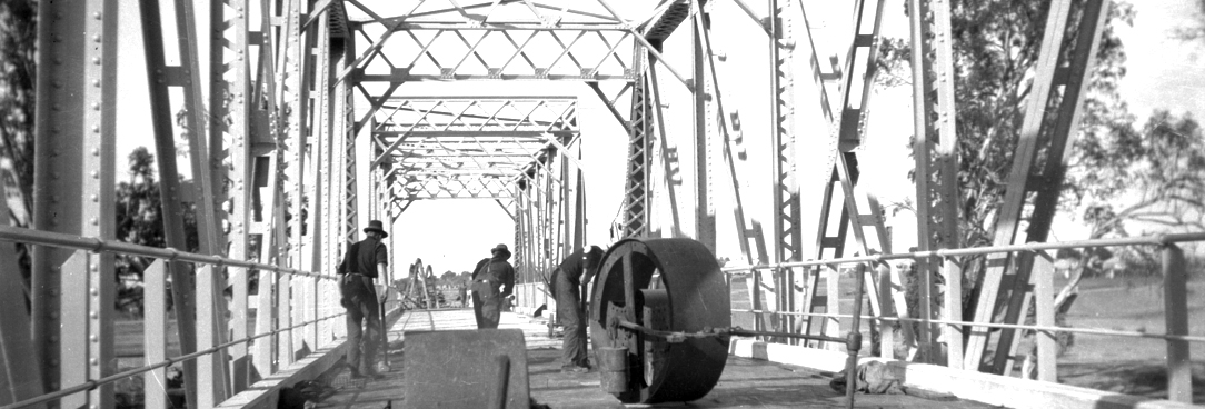 Black and white photo of men making road surface on bridge