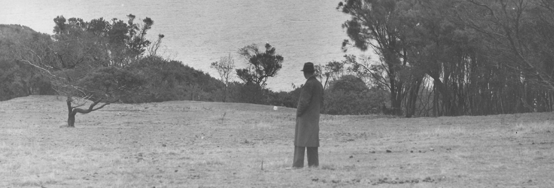 black and white photo of a man standing on a field