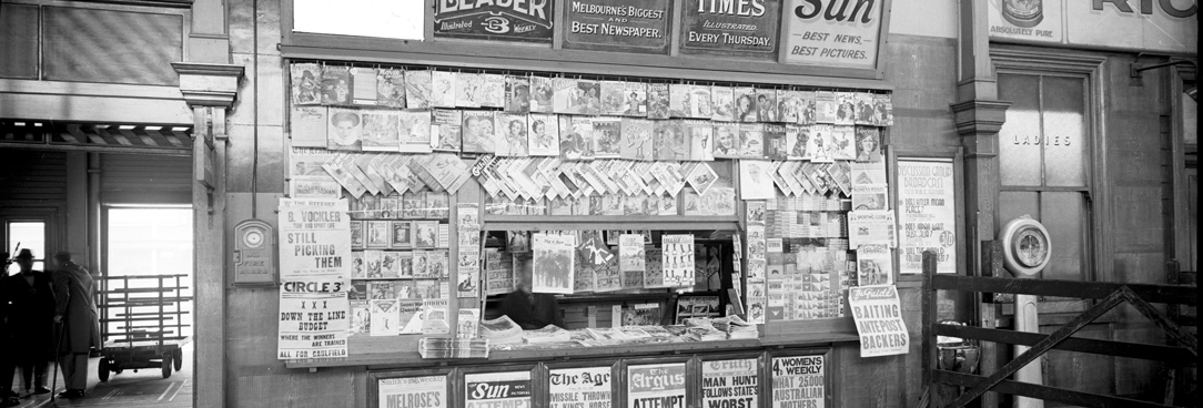Spencer Street main concourse newspaper kiosk with painted signs for The Age, The Sun, The Weekly Times and The Herald. 18TH July 1936. VPRS 12800/ P3  item ADV 1151