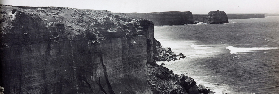 black and white photo of rocky mountain and ocean