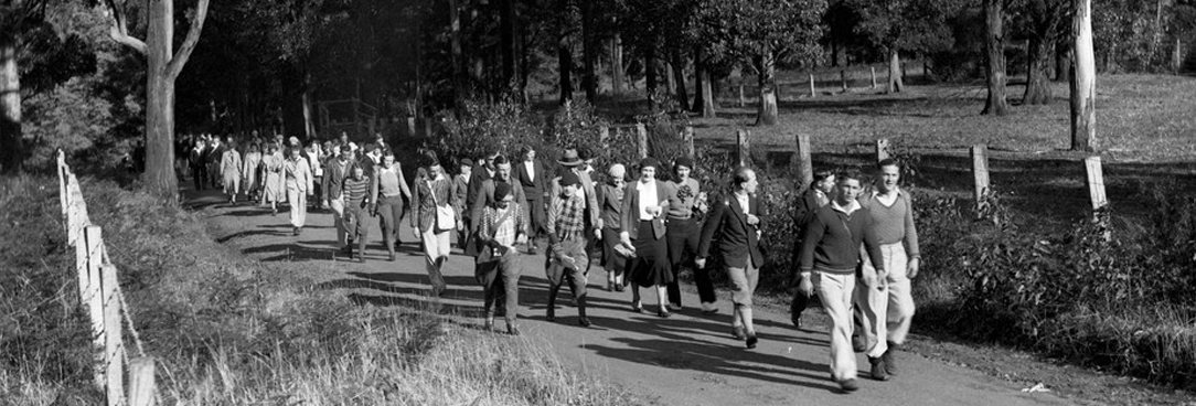 black and white photo of people dressed for a picnic on a hike