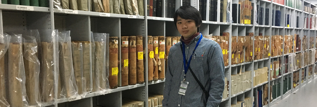 photo of a student standing in the archives repository