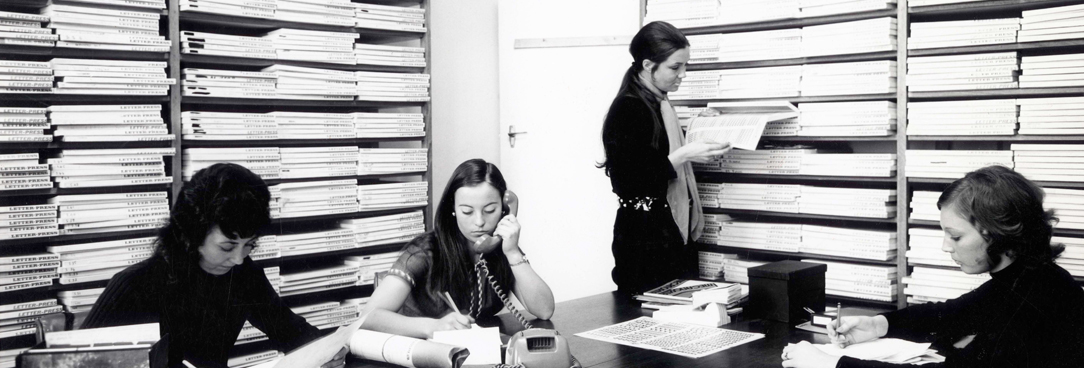black and white photo of women working at a large desk with lots of paper work stacked behind them
