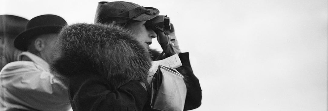 black and white photo of woman looking through binoculars