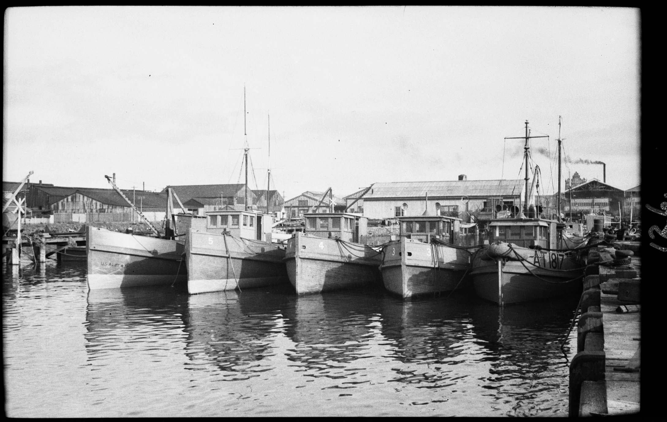black and white photo of boats docked