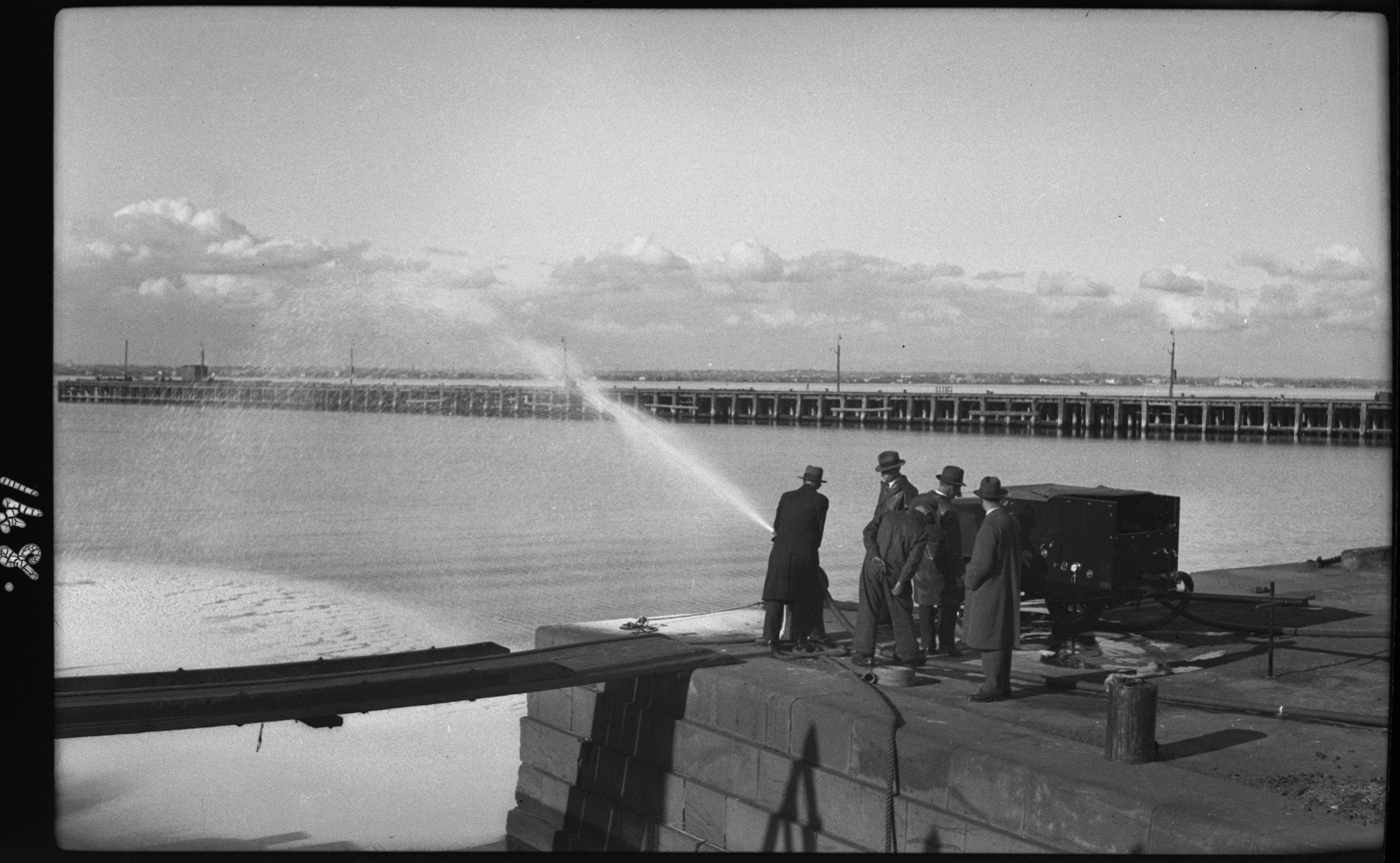 black and white image of men on dock using a large hose