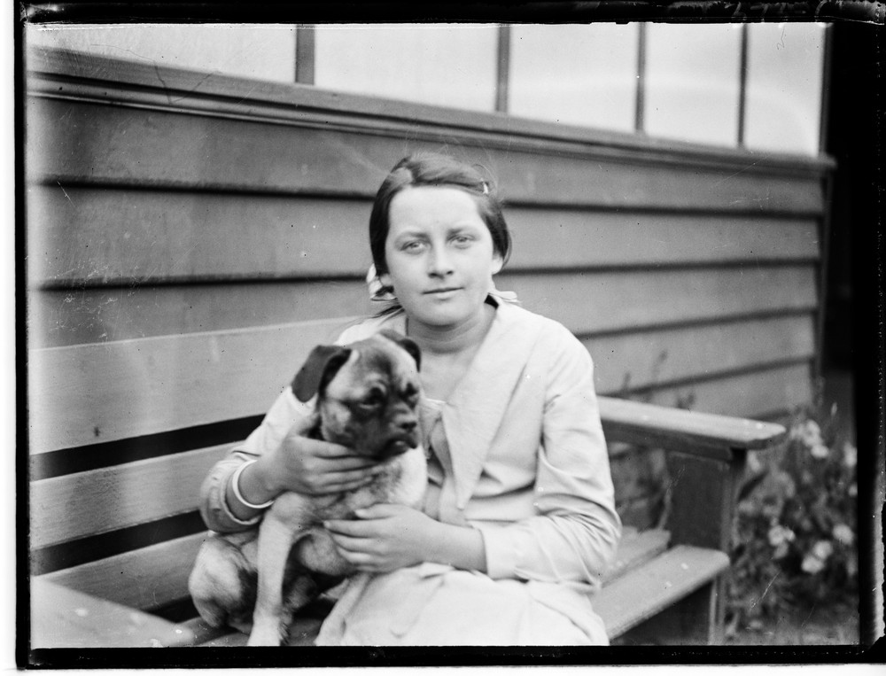 black and white photo of a woman holding a dog
