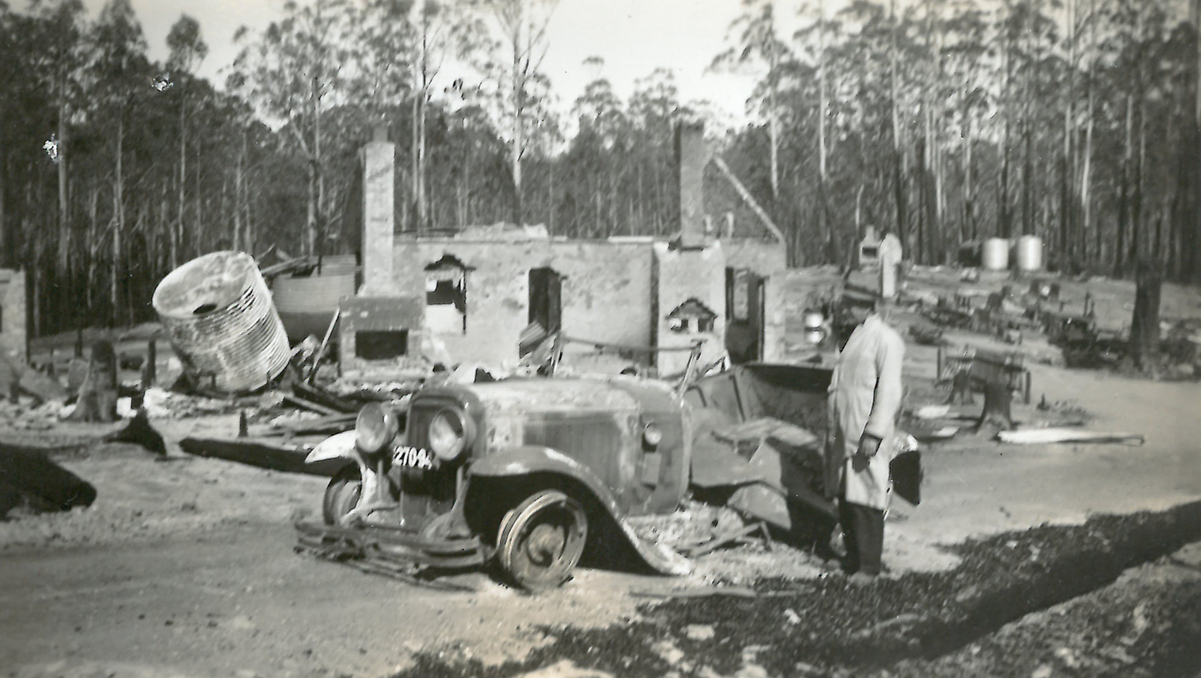 black and white photo of burned hut and car with man standing in front