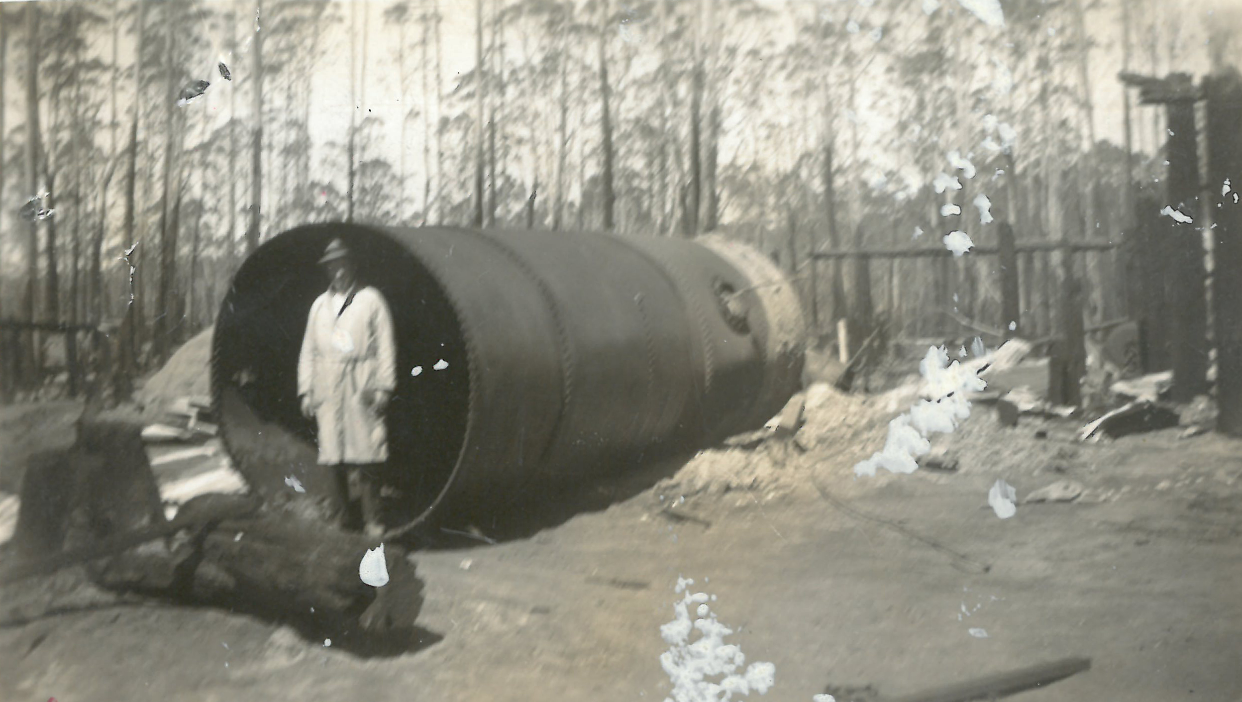 black and white photo of tank with burned landscape around and man in front