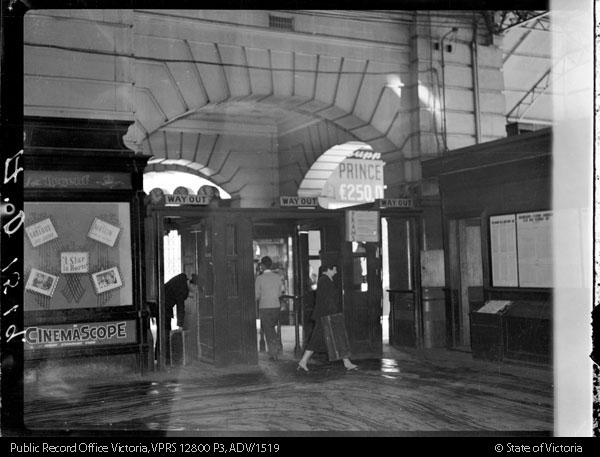 black and white photo inside Flinders Street Station with a pinboard in the background