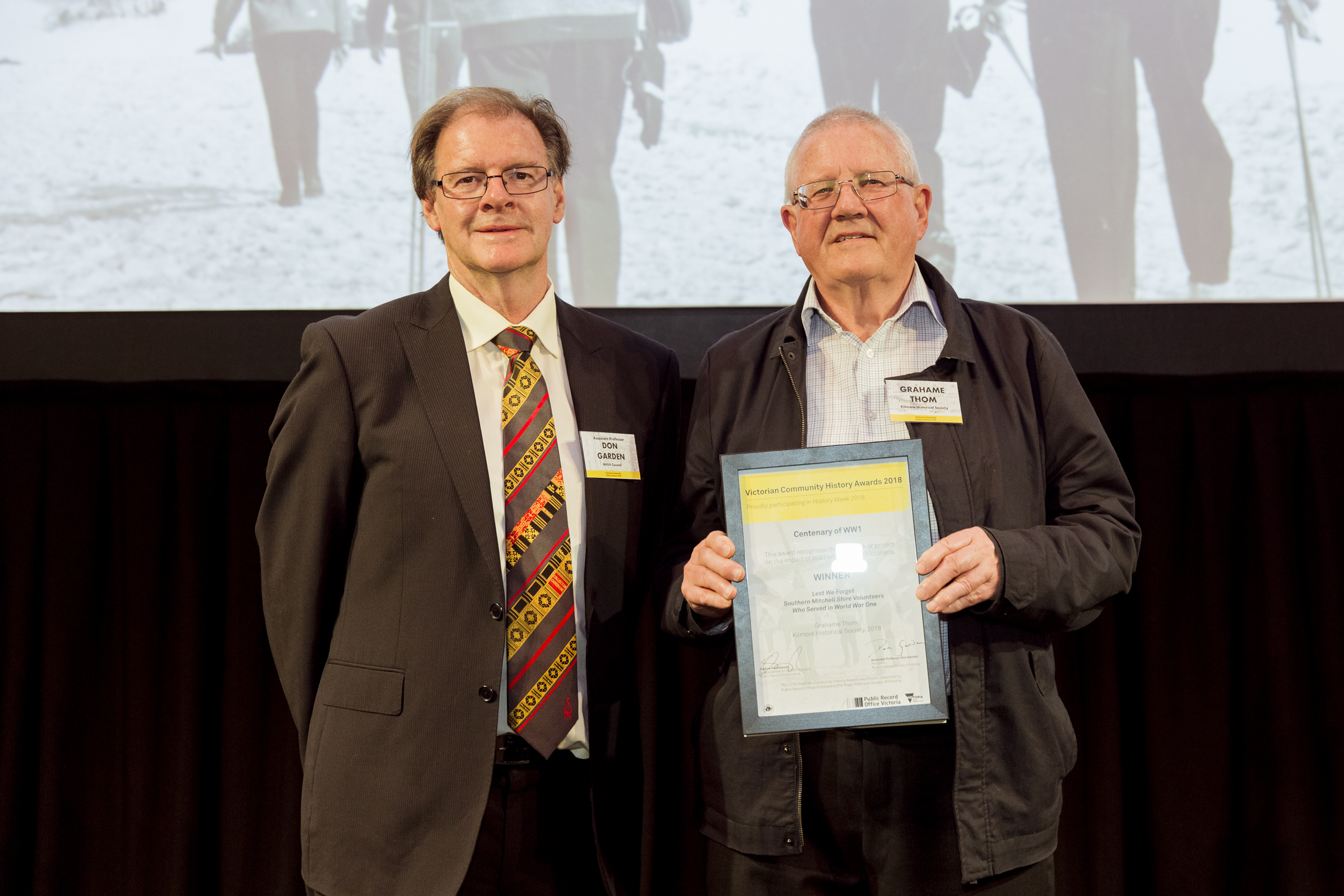 photo of two men standing side by side with one holding a certificate in his hands