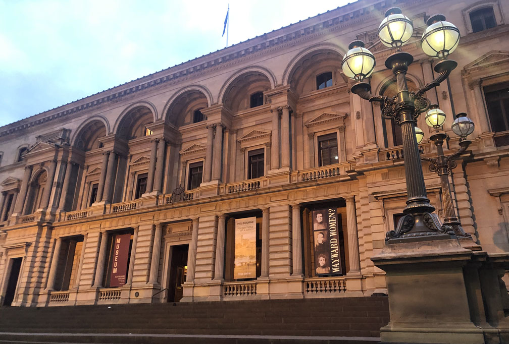 current photo of old treasury building, early evening, lights glowing