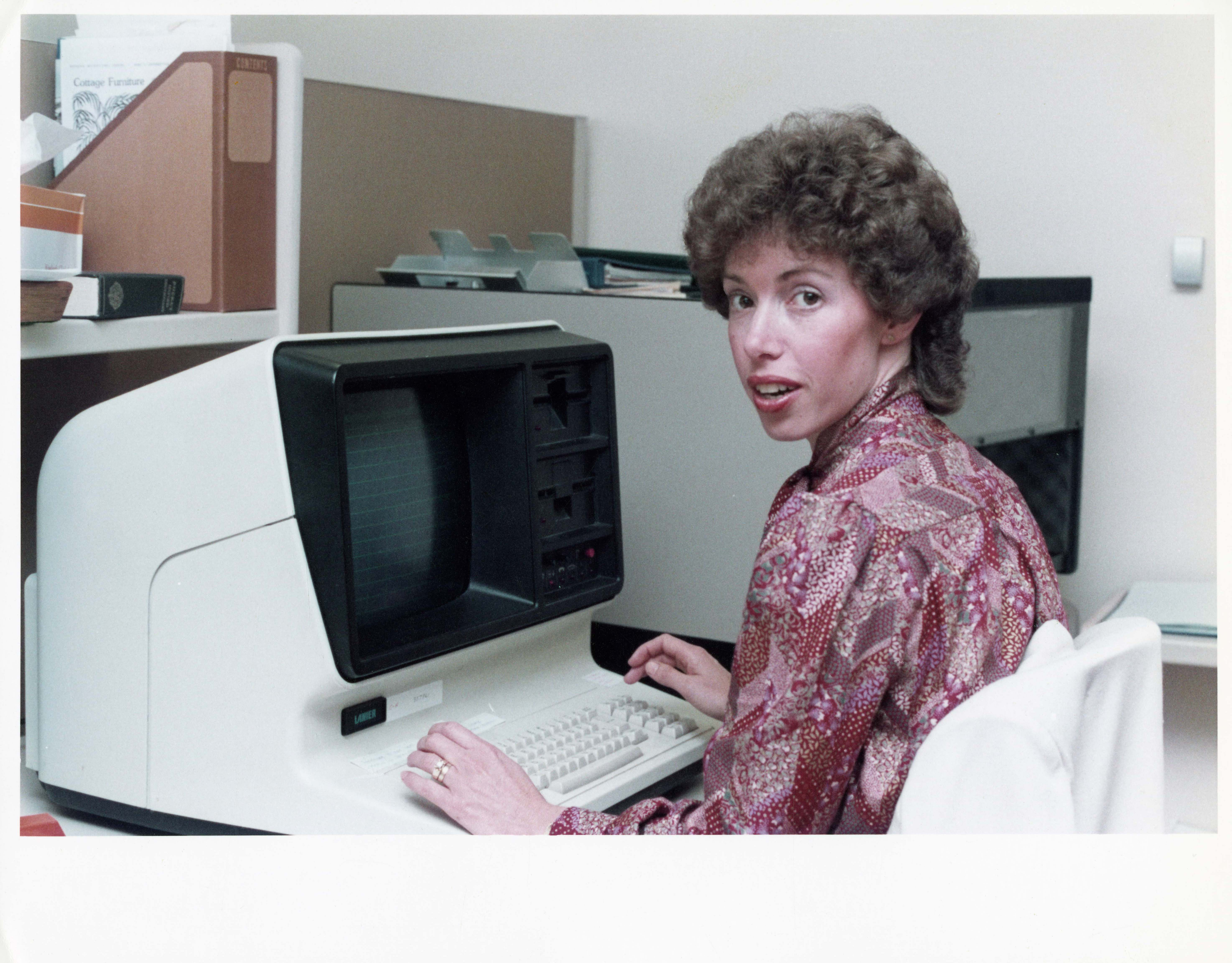 colour photo of a woman with an 80s perm typing at a large computer