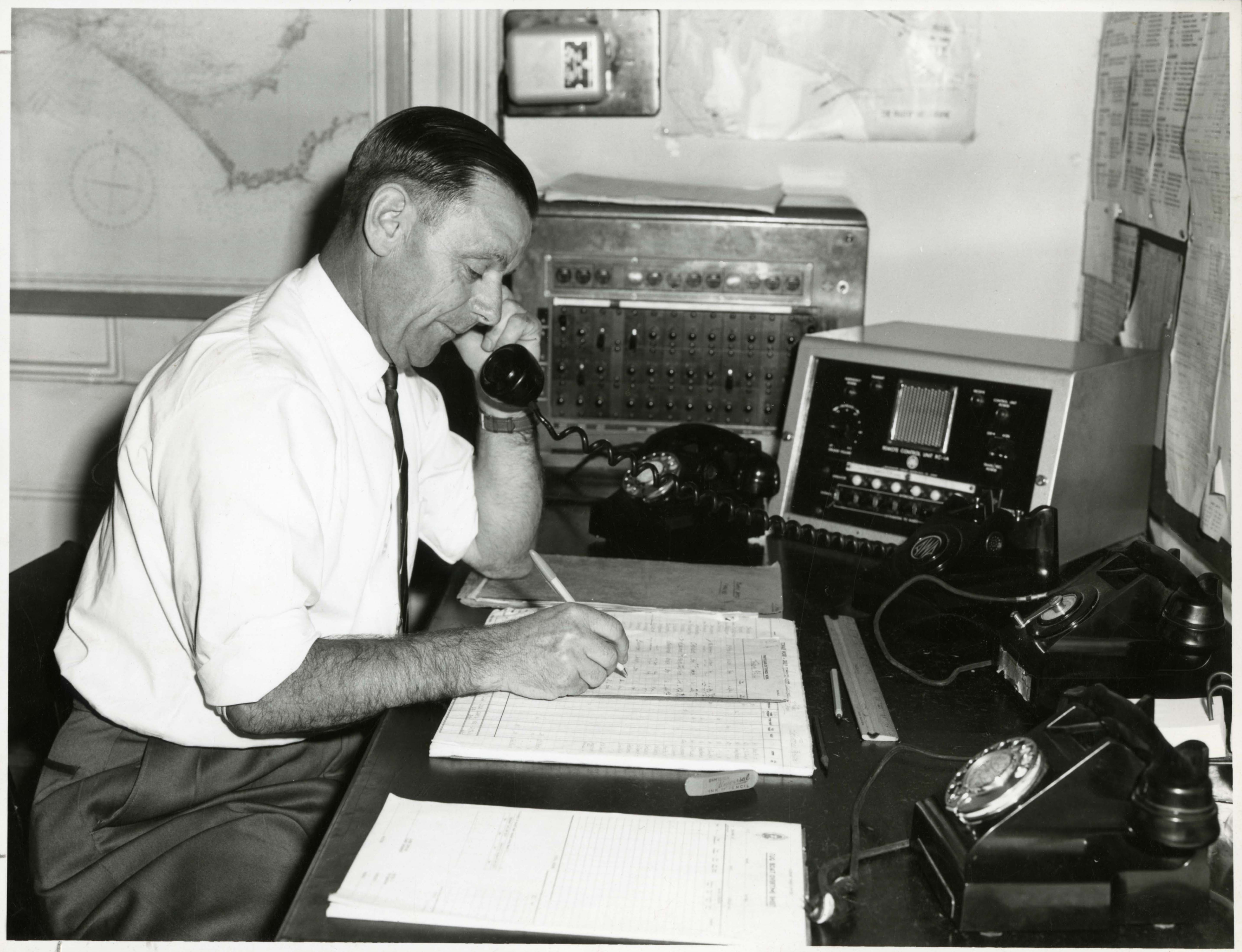 black and white photo man at desk with three phones, he is on one