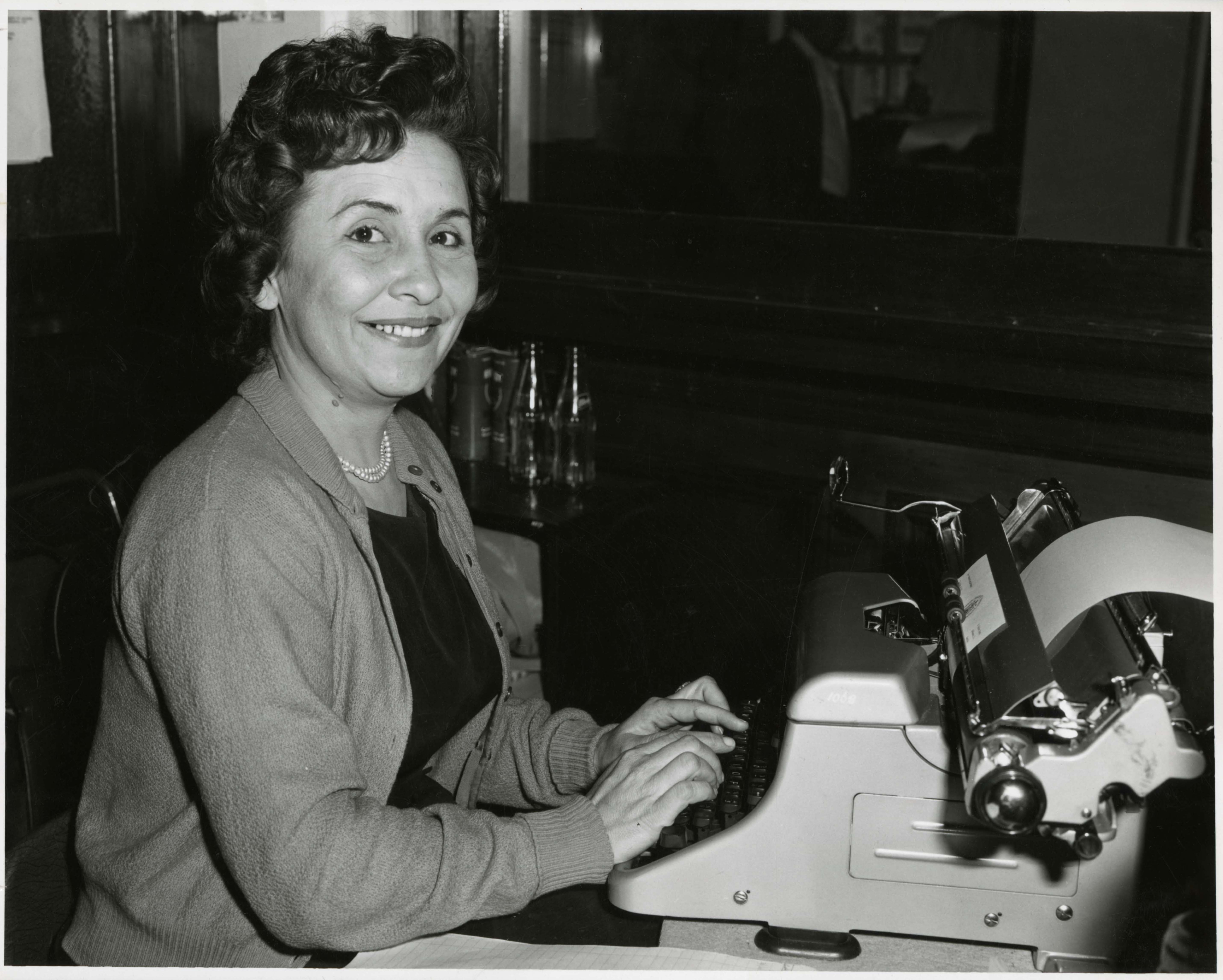 black and white photo of woman at a typewriter