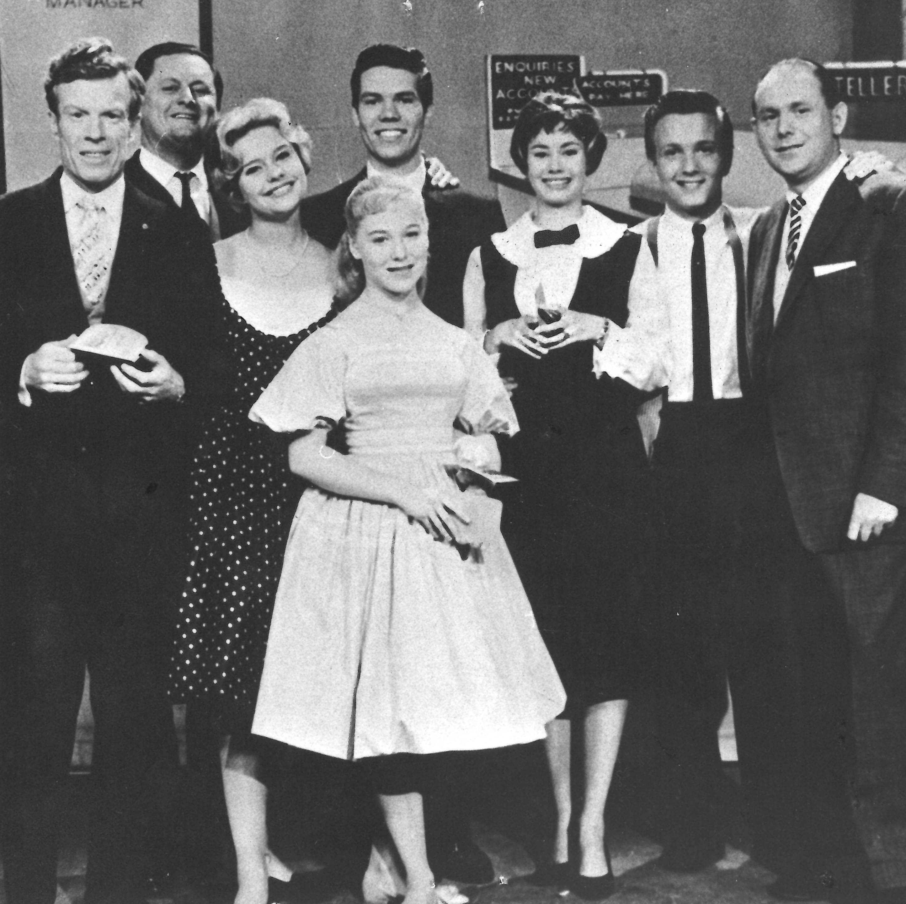 black and white photo of 8 people posing for the camera