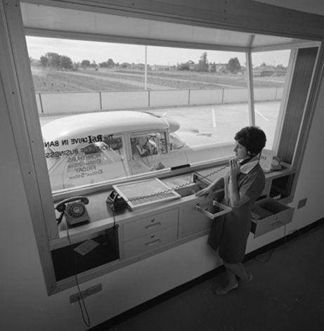 black and white photo of a drive in bank view from inside the bank where a staff member stands at the glass ready to serve the car on the other side
