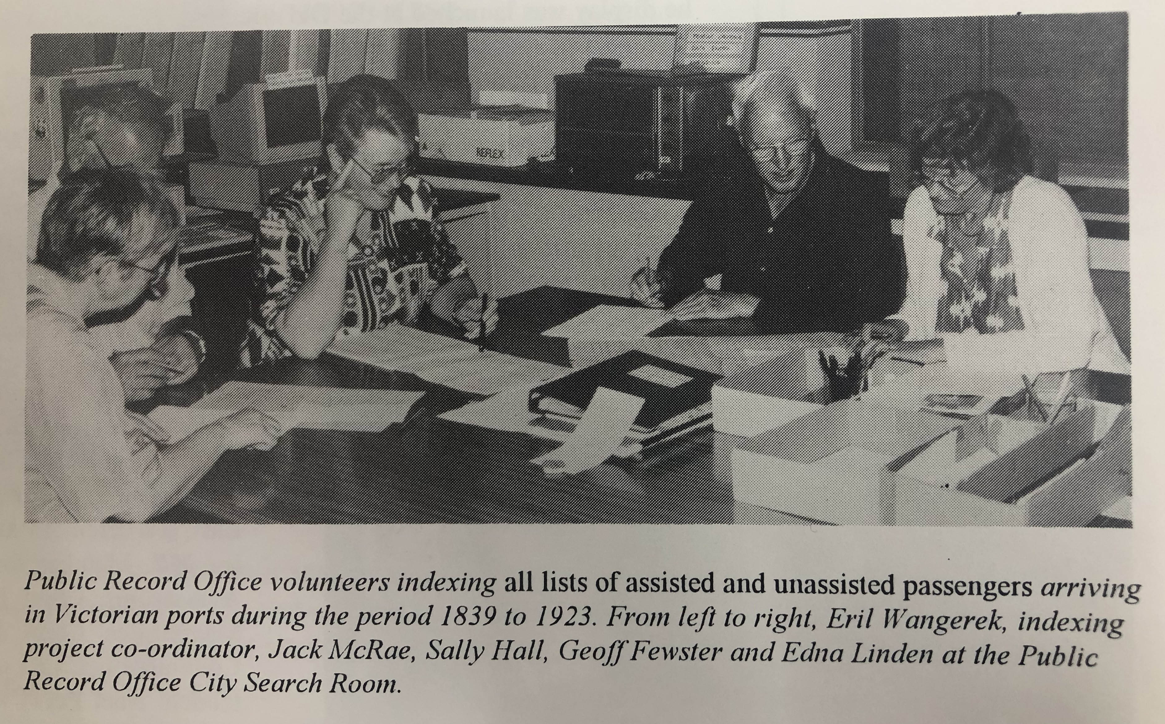 black and white photo of volunteers at a desk looking over documents