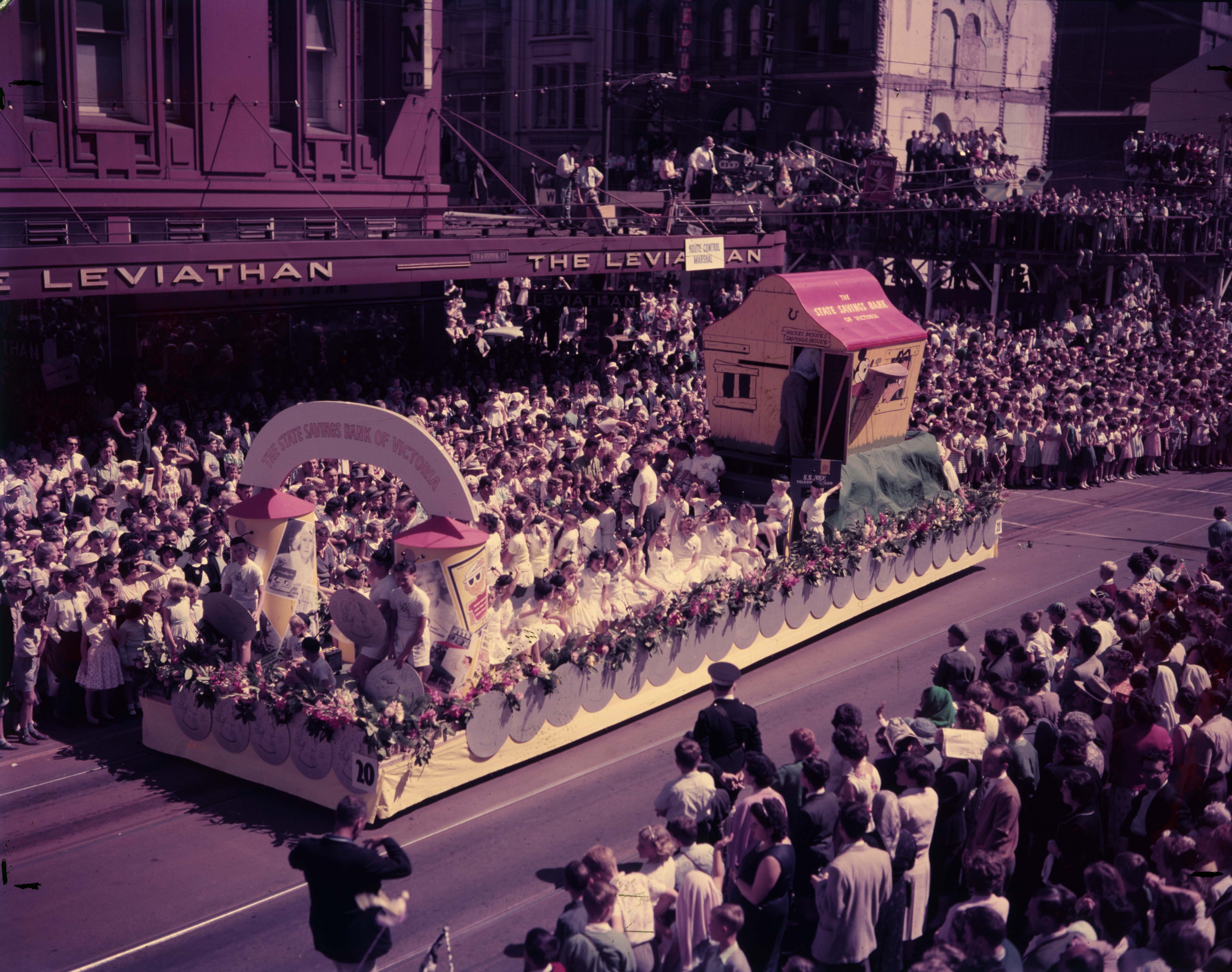 colour photo of the Mickey Mouse float headed down a packed Melbourne street during Moomba