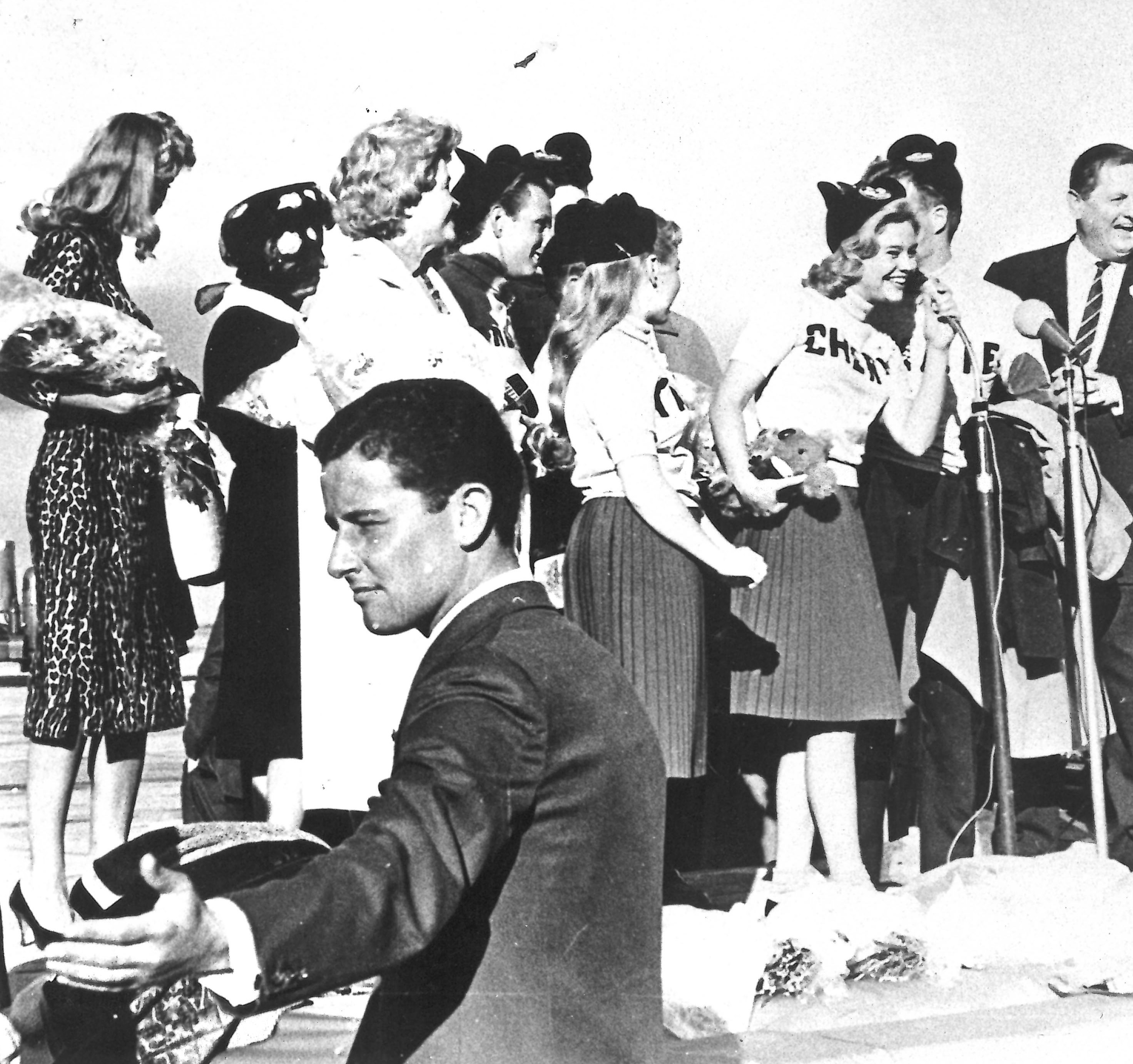 black and white photo of the mouseketeers speaking into microphones to waiting fans