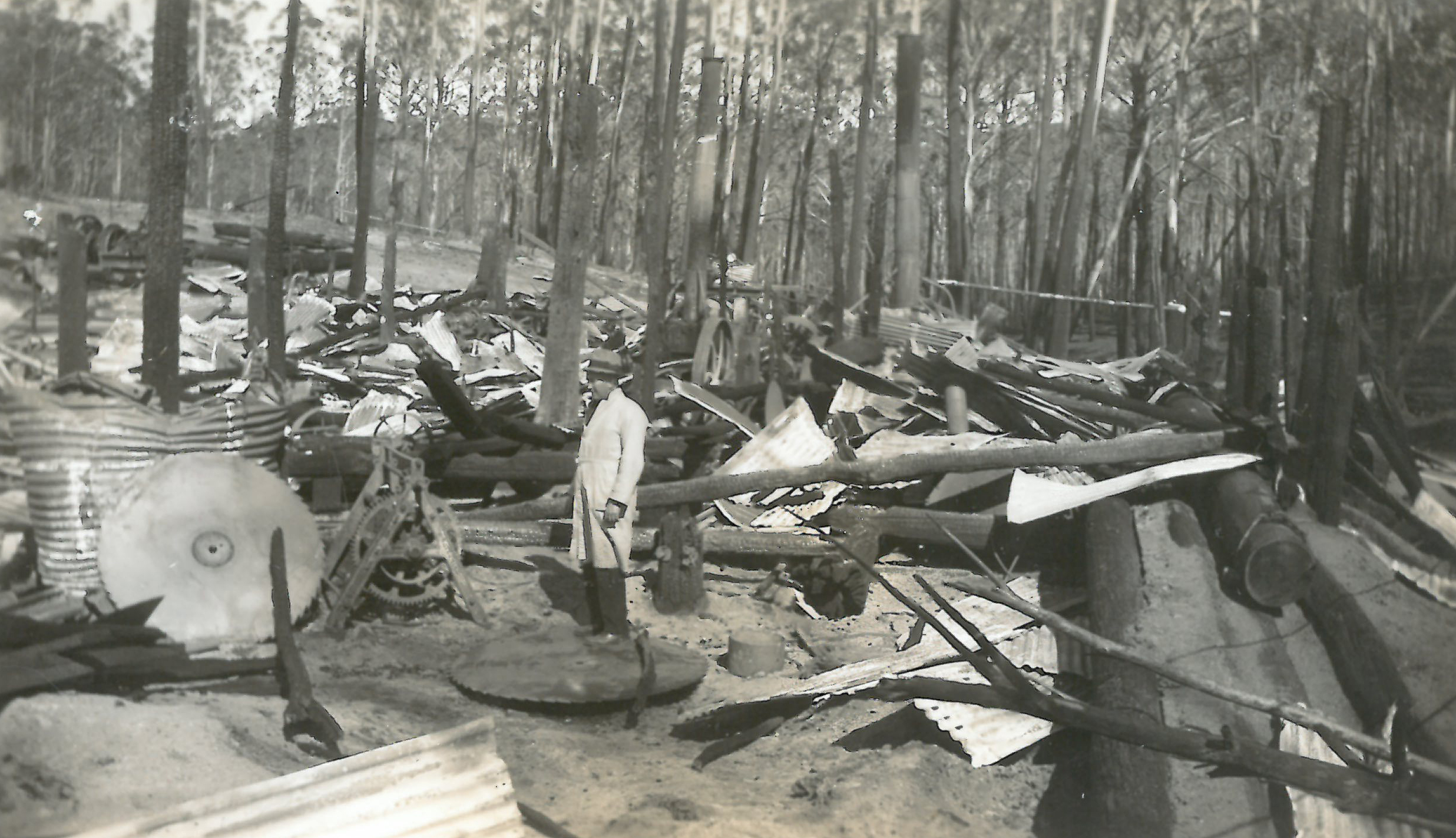 black and white photo of burned hut with man looking on