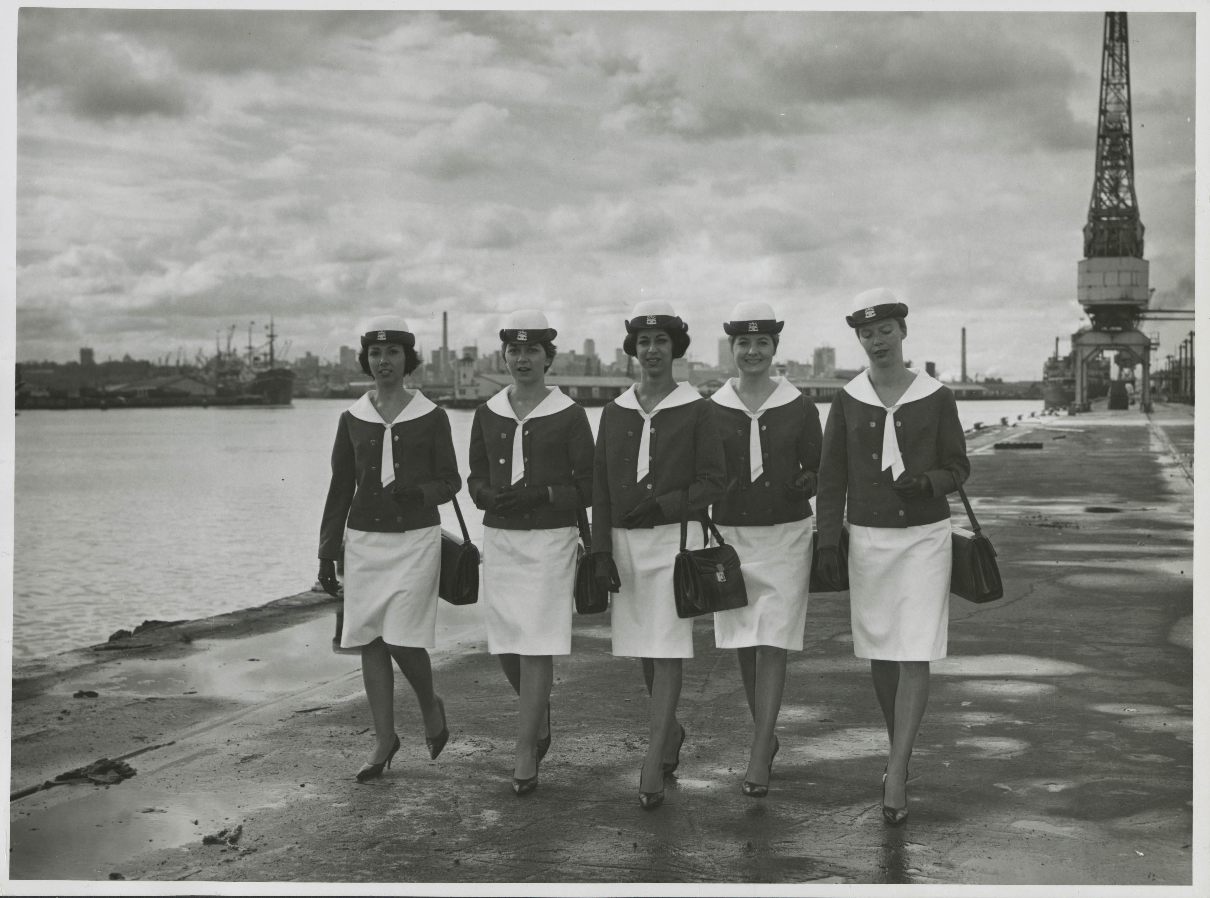 women in uniform walking along the dock