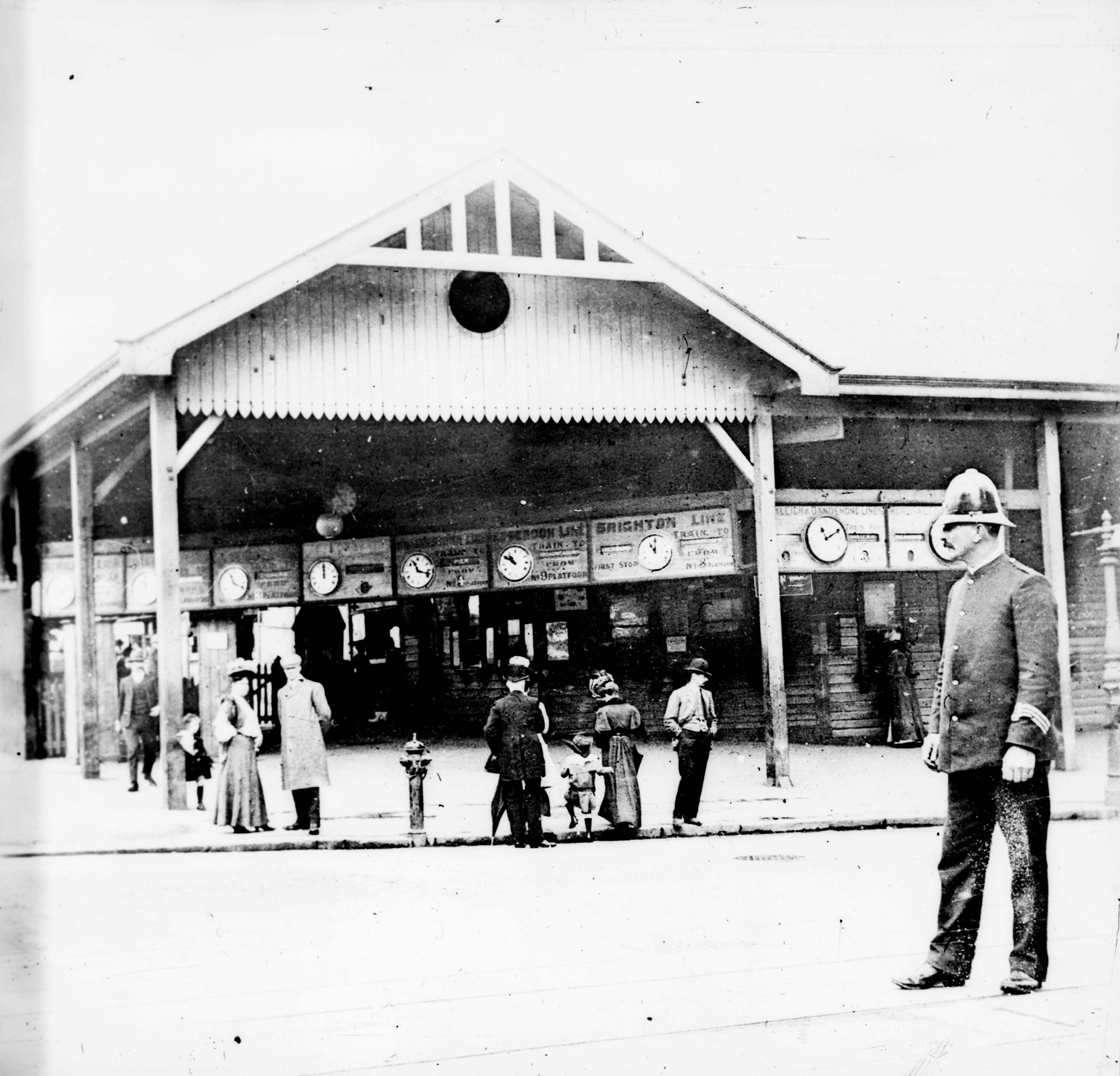 Black and white image of a police officer standing outside flinders street station