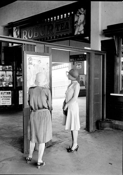 Women in 1920s/30s clothes looking at a sign