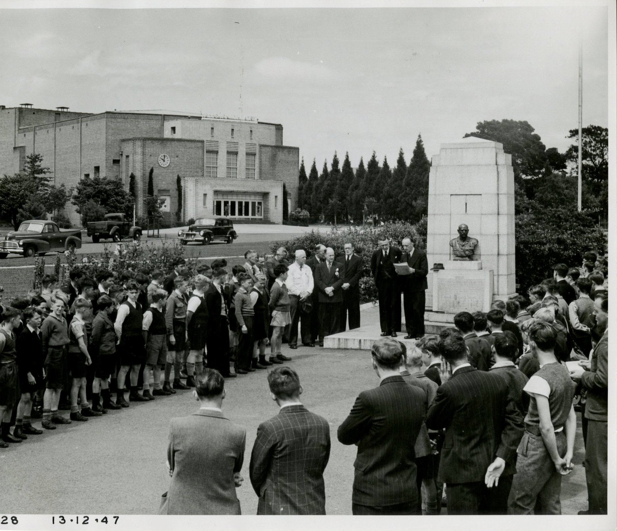 Crowd of men and school boys listening to a speech at a memorial