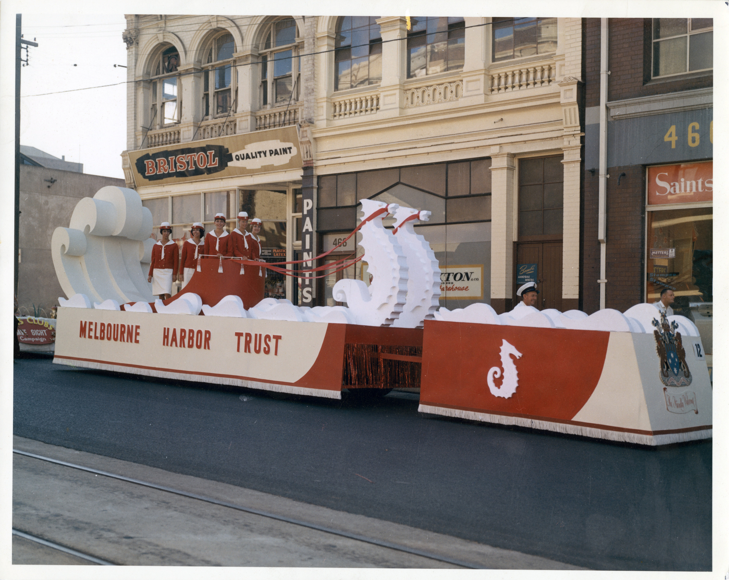 A red and white Melbourne Harbour Trust float with five women and two men in uniforms