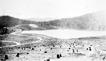 Photograph taken circa 1927 showing the reservoir, dam wall, roads, fencing and eastern hillside prior to planting and after the 1926 bush fire