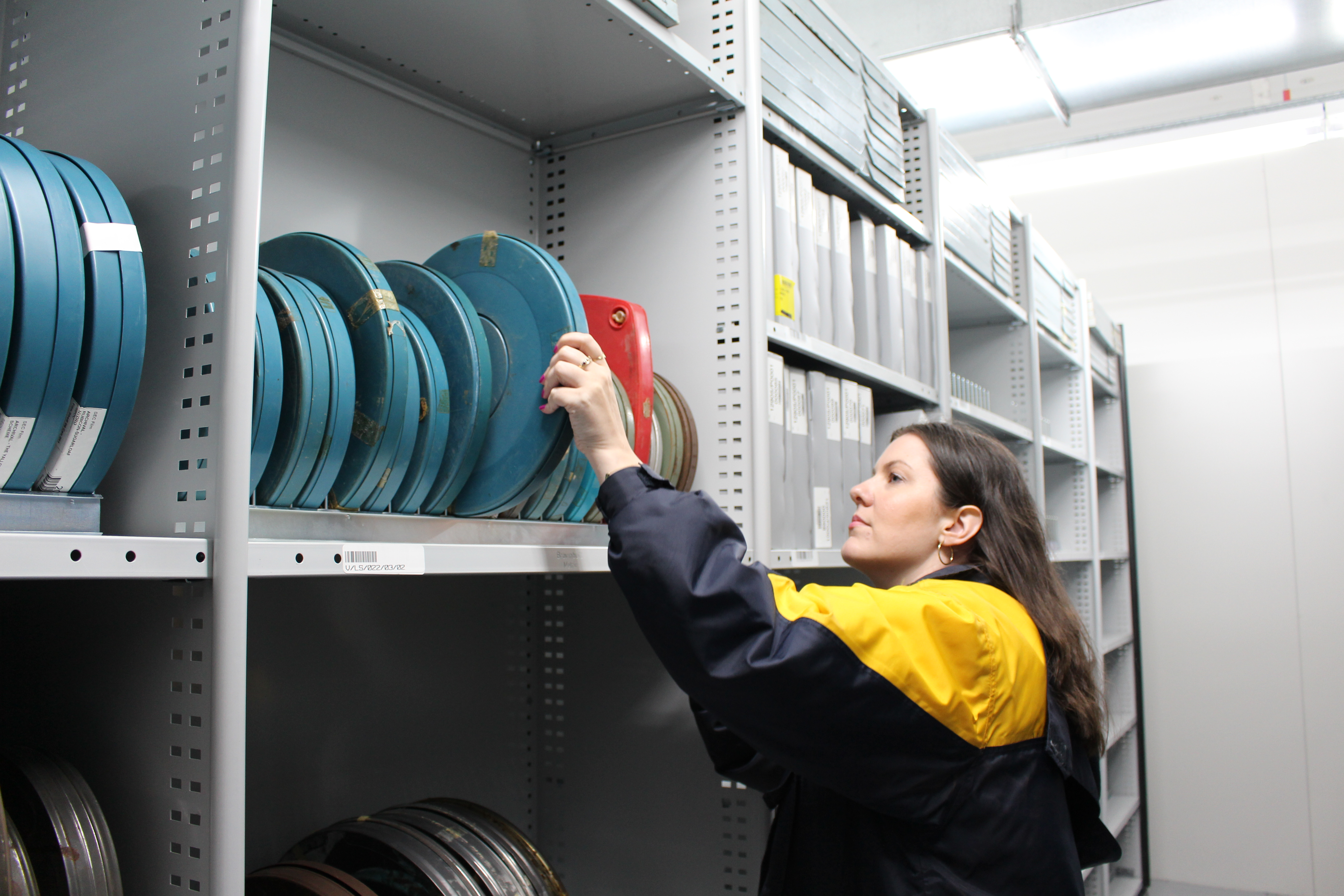 photo of woman taking a film reel from a shelf