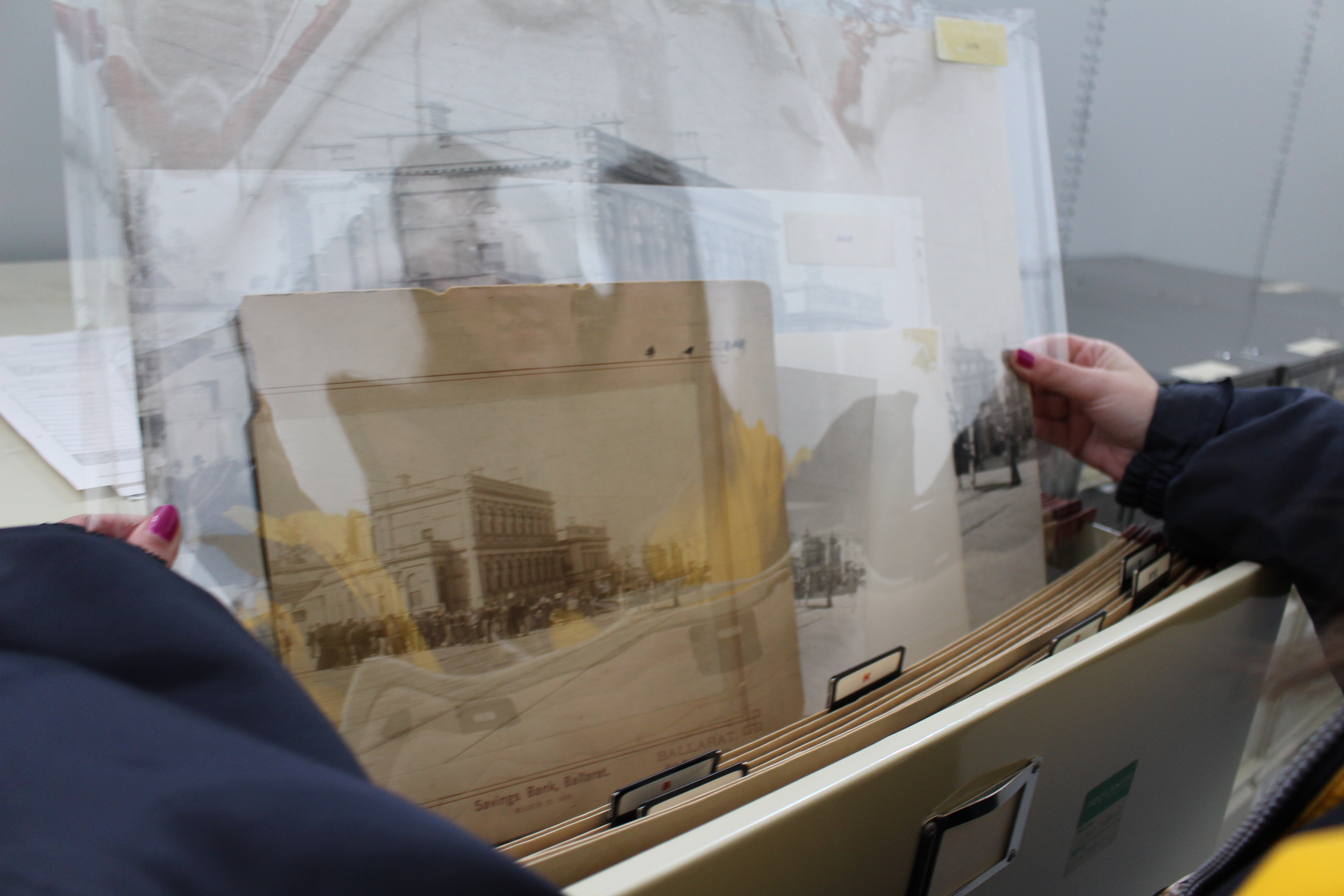 photo of photographs being pulled from a filing cabinet