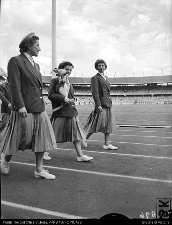 A photo of female athletes walking around the MCG with a toy kangaroo in their arms