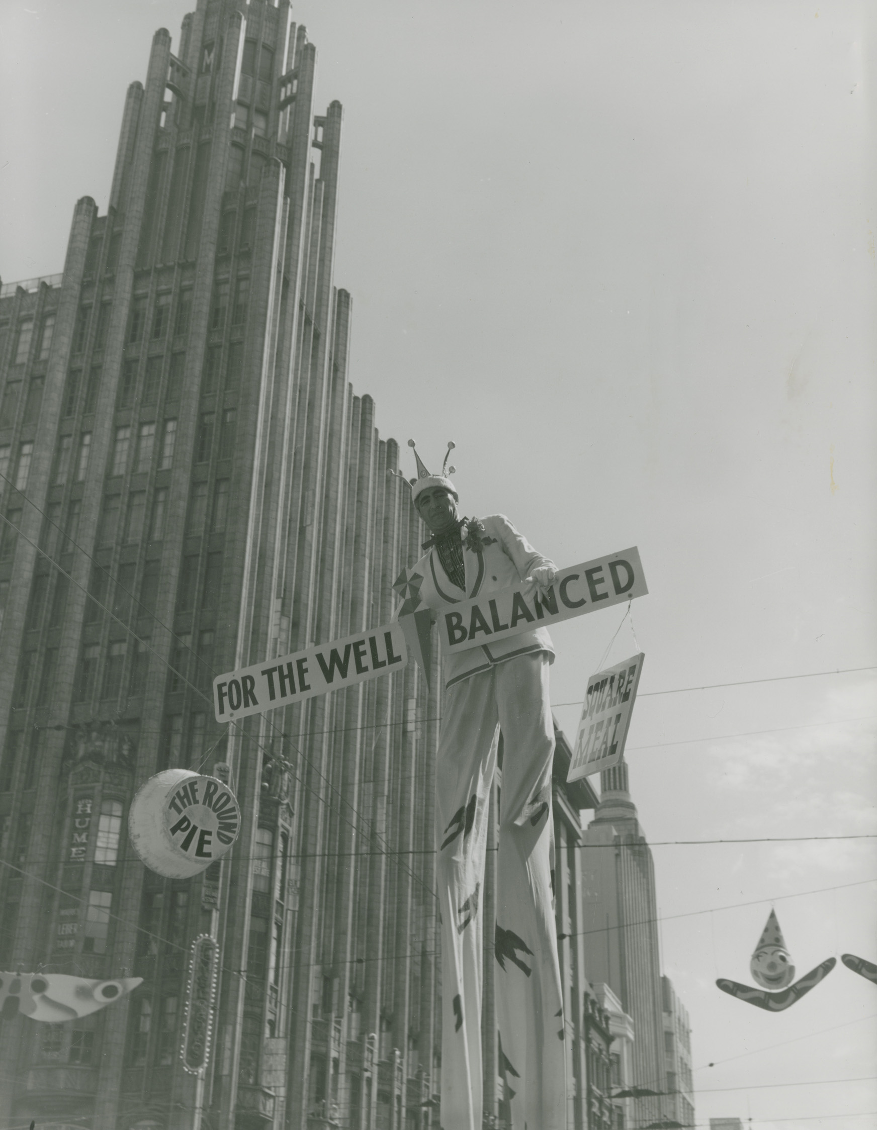 a man on stilts holding a sign that says 'for the well balanced'