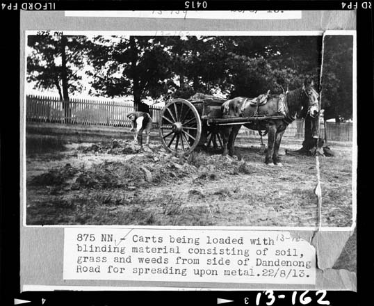 black and white photo of a horse and cart being loaded with construction materials
