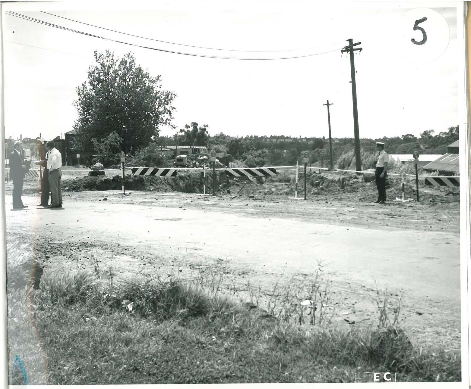 black and white photo of police standing on a dirt road