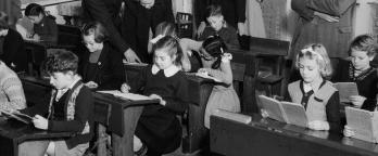 Black and white photo, school children in class