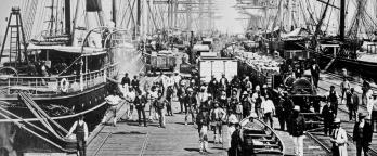 Black and white photo of people on pier with tall ships and pier donkey.