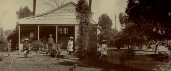Black and white photo of people in front of farmhouse