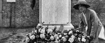 Black and white photo, woman lays flowers at a memorial